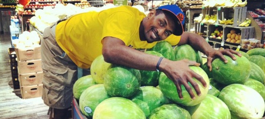 Metta World Peace in a Knicks hat hugging watermelons